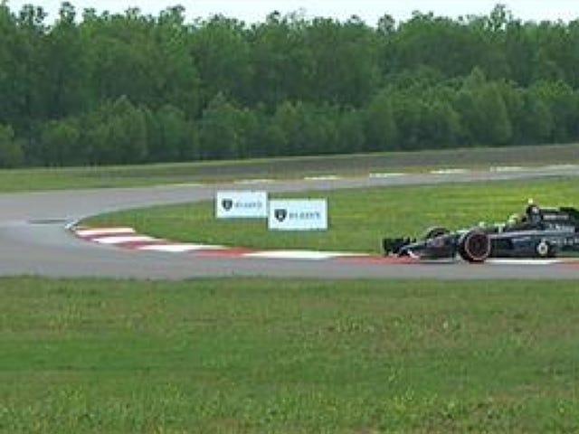 コーナーワーカーオブザイヤーがレースカーをトラックに押し戻す