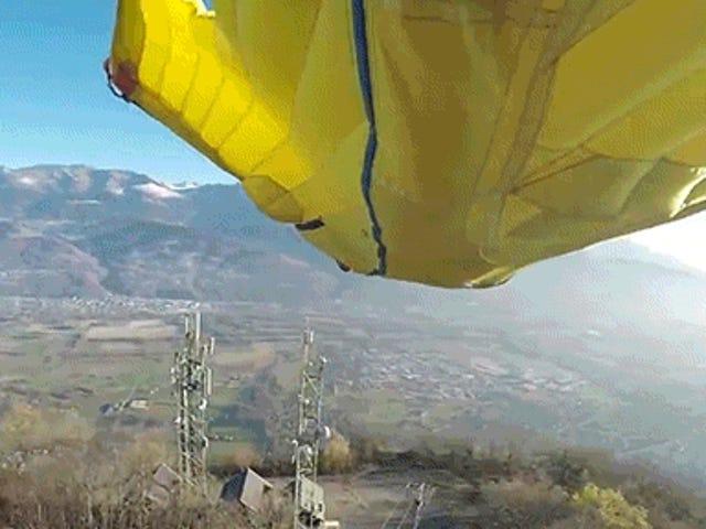 Hombre en traje de vuelo vuela a través de una estrecha abertura entre dos antenas