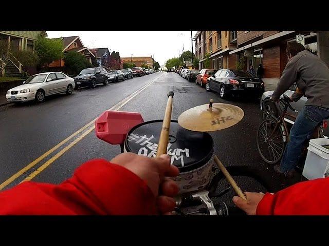 Greg Hum hat ein Schlagzeug auf seinem Fahrrad montiert