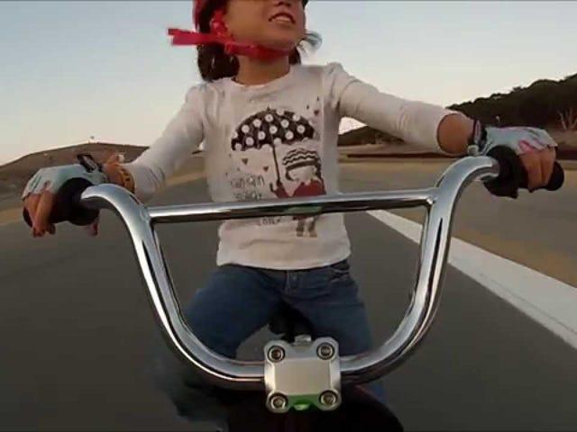 เด็กหญิงตัวเล็ก ๆ ขี่จักรยานลงที่เกลียวไขที่ Laguna Seca
