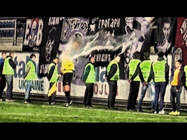 Des supporters serbes rudimentaires jettent un grand seau d'eau sur un arbitre