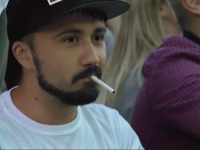 O fã extremamente fresco do campeonato do mundo ilumina o cigarro com sua carteira