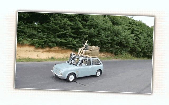 誰かが屋根に取り付けられたソファから日産パオを運転するのを見る