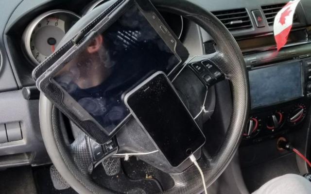 पुलिस ने स्टियरिंग व्हील के साथ टैबलेट और आईफोन के साथ ड्राइवर को रोक दिया