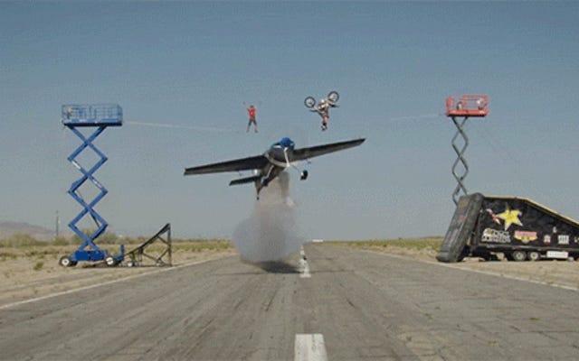 クレイジーな飛行機がバク転をしているバイカーと綱渡りをしている男の下を飛ぶ