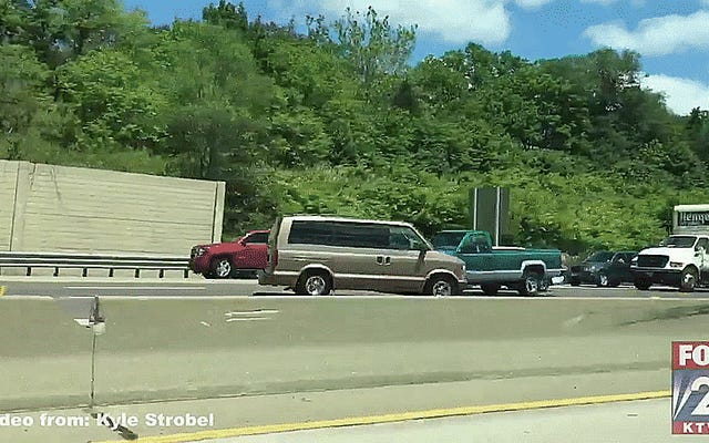 高速道路の反対側の警官から走っている銀行強盗とアイコンタクトをとる