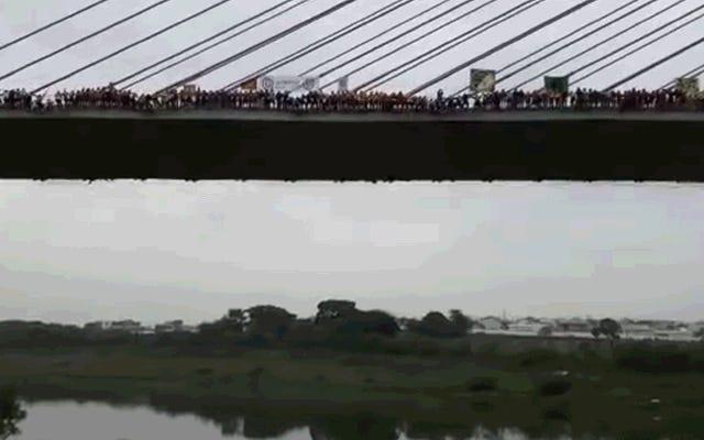 Veja 245 pessoas pularem e balançarem de uma ponte como uma cobra gigante pendurada