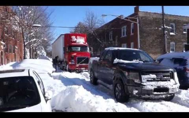 V6フォードF-150がシカゴの吹雪の中を大きなリグを牽引するのを見る