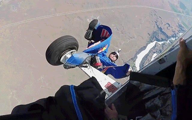 ビデオは飛行機に捕まるウイングスーツの男を示しています