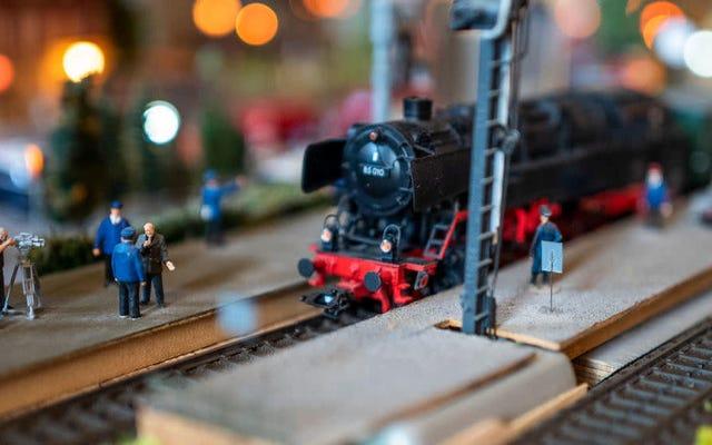 Guy ajusta la cámara al tren modelo, imaginando un mundo donde gatos gigantes deambulan por la Tierra