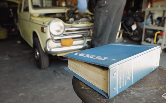 This Guy Is Fixing A 1972 Honda N600 By The Book, Which Is Kind Of Like A Car Forum But Printed On Paper