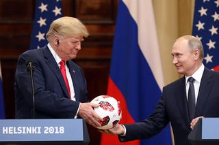 U.S. President Donald Trump, left, receives a soccer ball from Vladimir Putin, Russia's president, during a news conference in Helsinki, Finland, on Monday, July 16, 2018. Trump called Special Counsel Robert Mueller's probe into Russian election meddling a 'disaster' on Monday, again questioned whether Russia interfered in the 2016 election that he won and suggested he equally trusted his national intelligence director and Putin — all as he stood next to the Russian leader.