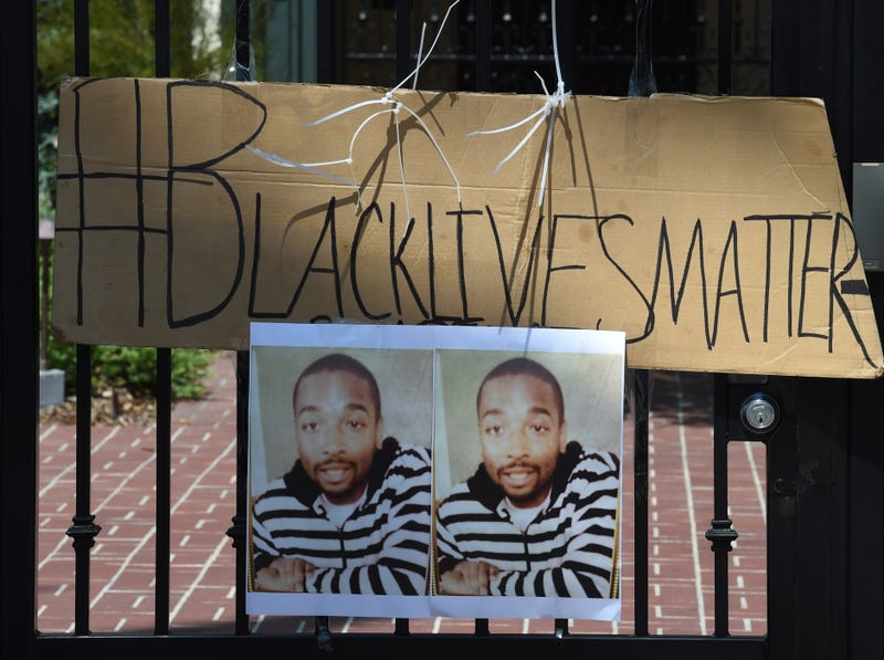 A sign displays an image of Ezell Ford as members of the Black Lives Matter alliance stage a protest outside the home of Los Angeles Mayor Eric Garcetti on June 7, 2015, as they demand that he fire Los Angeles Police Chief Charlie Beck in the wake of the fatal police shooting of Ford in August 2014. MARK RALSTON/AFP/Getty Images