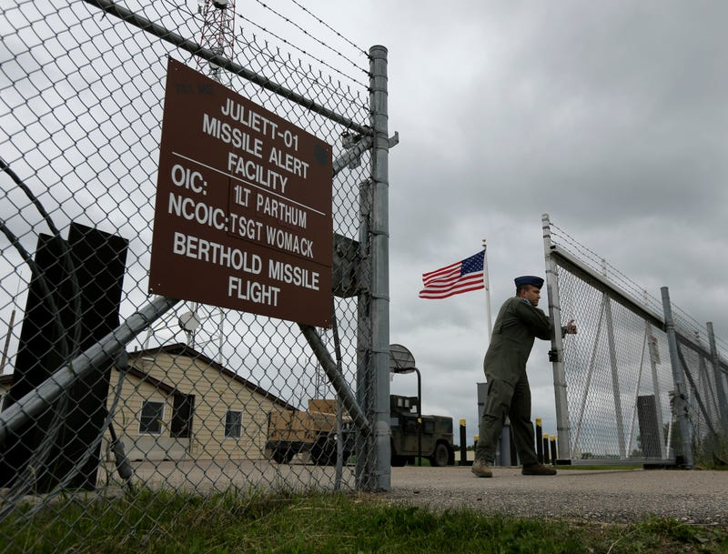 In this photo taken June 24, 2014, Capt. Robby Modad closes the gate at an ICBM launch control facility in the countryside outside Minot, N.D. Launch control officers working from a secure capsule far underground the complex control 10 Minuteman 3 missiles carrying nuclear warheads spread out in the fields around the facility. (AP Photo/Charlie Riedel)