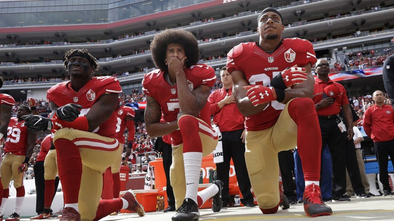 Colin Kaepernick, center, takes a knee during the national anthem, sparking a national debate about athletes and social activism.