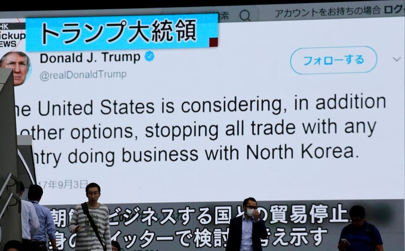 People walk by a TV news program showing tweets from U.S. President Donald Trump while reporting North Korea's nuclear test, in Tokyo, Monday, Sept. 4, 2017. (AP Photo/Shizuo Kambayashi)