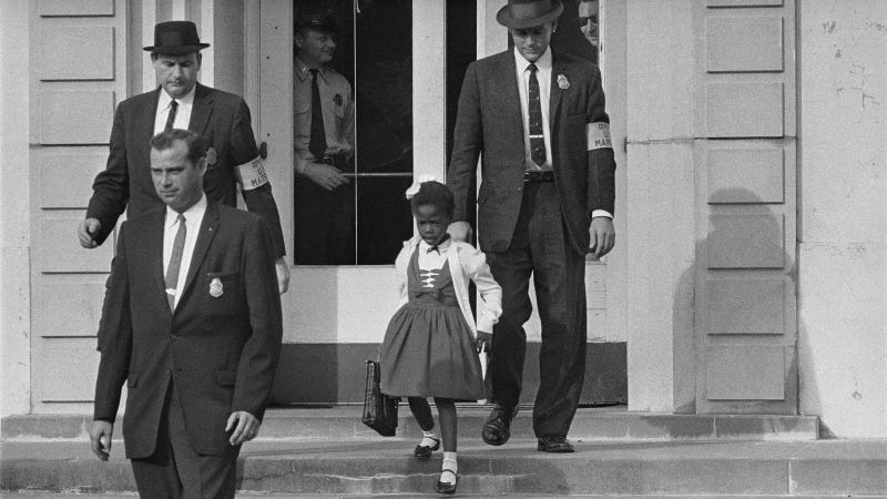 U.S. Deputy Marshals escort six-year-old Ruby Bridges from William Frantz Elementary School in New Orleans, La., in Nov. 1960. The first grader is the only black child enrolled in the school, where parents of white students are boycotting the court-ordered integration law and are taking their children out of school. Photo via AP Images.