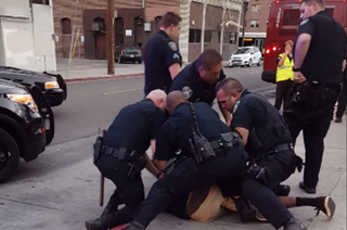 Stockton, Calif., police officers tackle and arrest a teen for jaywalking. YouTube screenshot