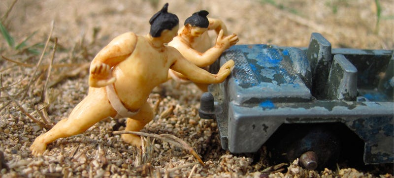 Illustration for article titled Tiny Sumo Wrestlers Pushing A Derelict Jeep Need A Haiku Caption