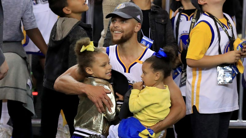 Stephen Curry of the Golden State Warriors celebrates holding his daughters Riley and Ryan after defeating the Cleveland Cavaliers 129-120 in Game 5 to win the 2017 NBA Finals on June 12, 2017 in Oakland, California.