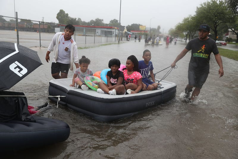 People use an air mattress to float down a flooded street as they evacuate their homes after the area was inundated with flooding from Hurricane Harvey on ...