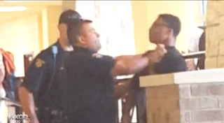 Video footage shows a police school resource officer grabbing 14-year-old Gyasi Hughes by the throat before throwing him to the floor at Round Rock High School in Round Rock, Texas, on Oct. 8, 2015.KXAN screenshot