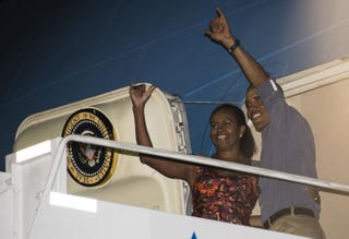 President Barack Obama and first lady Michelle Obama wave to well-wishers as they prepare to board Air Force One in Honolulu before returning to Washington, D.C., at the end of their vacation Jan. 3, 2015.NICHOLAS KAMM/AFP/Getty Images