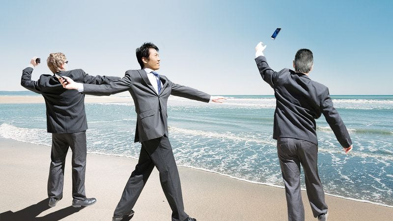 Three businessmen throwing their cell phones into the ocean.