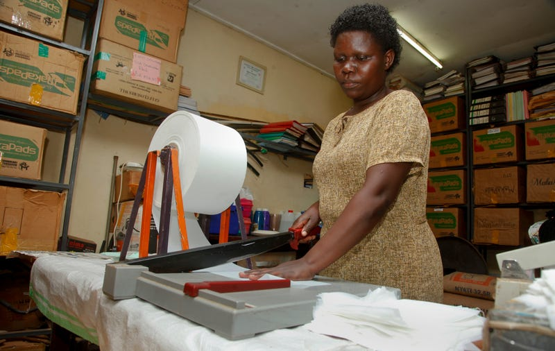 In this 2017 photo a worker cuts locally made biodegradable sanitary pads known as Makapads, made from waste paper with papyrus as the absorbent, that sell for half the price of imported pads, at the factory in Kampala, Uganda. Menstrual hygiene has emerged as a serious, and often emotional, subject in Africa, where some experts say governments must supply free sanitary pads to girls who are often at risk of dropping out of school because of embarrassment. AP Photo/Stephen Wandera