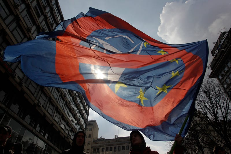 A man waves an anti NATO and EU flag during an anti NATO rally in downtown Belgrade, Serbia, March 27, 2016. Thousands marched against NATO and the West in Serbia, carrying pro-Russian banners praising Russian President Vladimir Putin. Pro-Russian forces in Serbia have been gaining ground ahead of the April 24 general election that could decide which way Serbia is heading, toward Russia or EU. (AP Photo/Andrej Cukic)