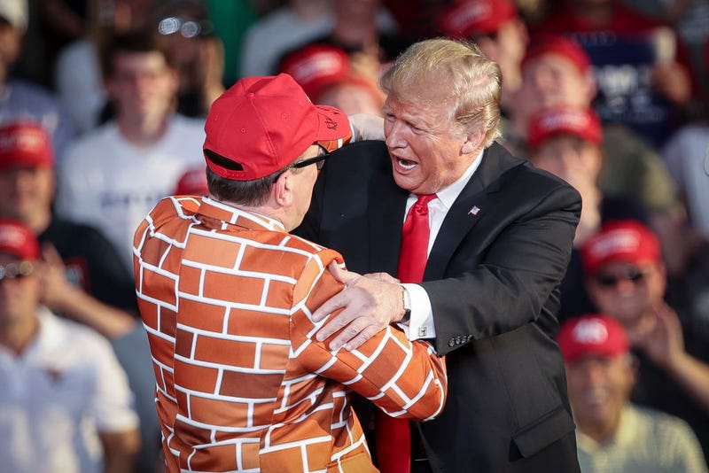 President Donald Trump calls up Blake Marnell, wearing a jacket with bricks representing a border wall, to the stage during a 'Make America Great Again' campaign rally.