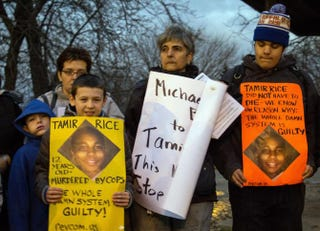 People display signs at Cudell Commons Park in Cleveland Nov. 24, 2014, during a rally for Tamir Rice, a 12-year-old boy shot by police Nov. 22.JORDAN GONZALEZ/AFP/Getty Images