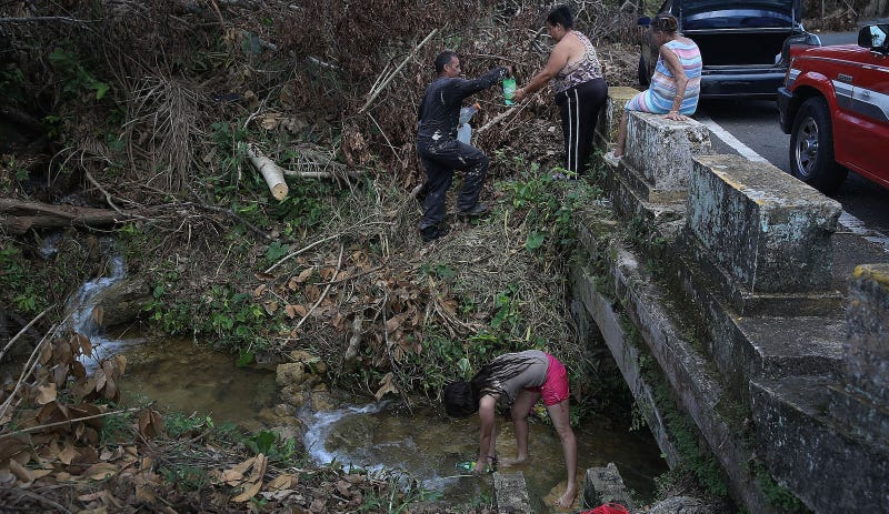 Puerto Rican residents collect water from a stream. Image via Getty.