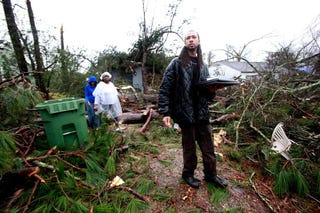 Jevern Gillispie (right) helps bring out belongings from Lisa Hill and Elunion Cooper's home after a tornado touched down  Feb. 11, 2013, in Hattiesburg, Miss.  (Sean Gardner/Getty Images)