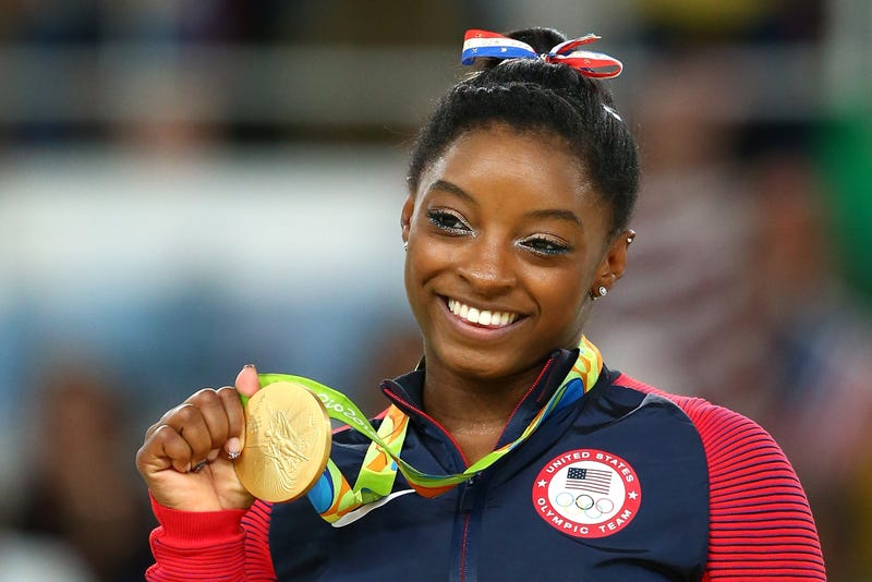 Gold medalist Simone Biles celebrates on the podium at the medal ceremony for women's gymnastics at the 2016 Olympic Games on Aug. 16, 2016, in Rio de Janeiro.Alex Livesey/Getty Images