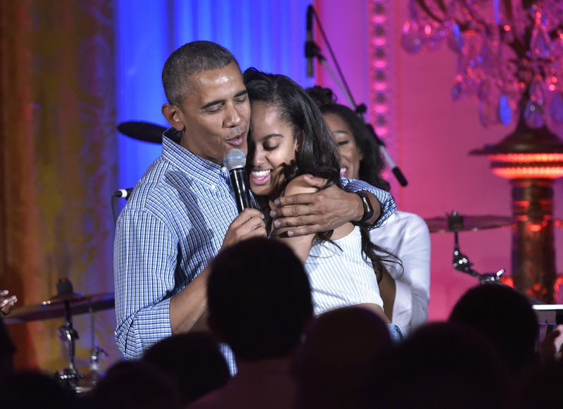 US President Barack Obama hugs his daughter Malia on her birthday during an Independence Day Celebration for military members and administration staff on July 4, 2016 in the East Room of the White House in Washington, D.C.MANDEL NGAN/AFP/Getty Images