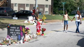 Lakiah Payne (left) walks with Michael Brown's sister, Deja Brown, as they visit a memorial for him that is set up on the spot where he fell after he was shot by police on Aug. 19, 2014, in Ferguson, Mo.Joe Raedle/Getty Images