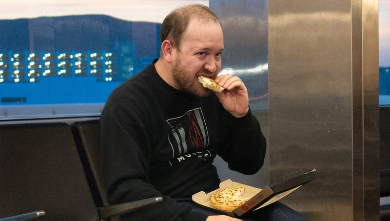 Illustration for article titled Man Silently Eating Personal Pan Pizza Alone In Corner Of Airport Unaware This Will Be Best Part Of 7-Day Vacation