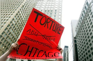 Adam Turl displays a sign regarding police torture during a demonstration July 21, 2006, in downtown Chicago.Tim Boyle/Getty Images