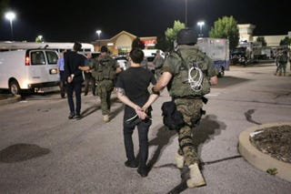 Members of the St. Louis County Police tactical team take two journalists into custody on Aug. 19, 2014.  Lukas Hermsmeier, left, a reporter for Bild, a German newspaper, and Ryan Devereaux, a reporter for theintercept.com, were in the area when police arrived. David Carson/St. Louis Post-Dispatch