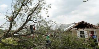 Volunteers chainsaw a fallen tree in Shawnee, Okla. (Brett Deering/Getty Images)