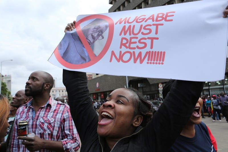 A woman holds up a banner among crowds marching on the streets of Harare, Zimbabwe, on Nov. 18, 2017, demanding the departure of President Robert Mugabe. (Tsvangirayi Mukwazhi/AP Images)