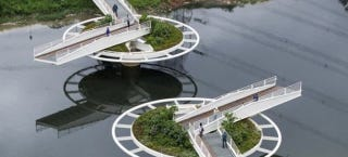Illustration for article titled This Footbridge Spins Open on Two Giant Wheels to Let Boats Pass