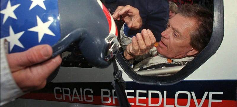 """Former land speed record holder Craig Breedlove reaches for his helmet prior to making his first test run in his car """"Spirit of America"""" Wednesday, Oct 23, 1996, in the Black Rock Desert near Gerlach Nev. (AP Photo/Rich Pedroncelli)"""
