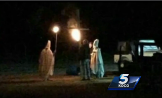 Cary Sharp and friends dressed as Ku Klux Klan members carrying torches near a cross in Lahoma, Okla., Oct. 31, 2015KOCO screenshot