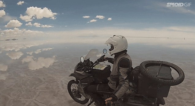 Riding a motorcycle on mirrored salt flats looks like flying in the sky