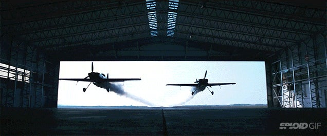 Two planes crazily fly through a hangar in an epic stunt