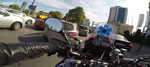 First person view of a motorcycle ambulance driving with its siren on