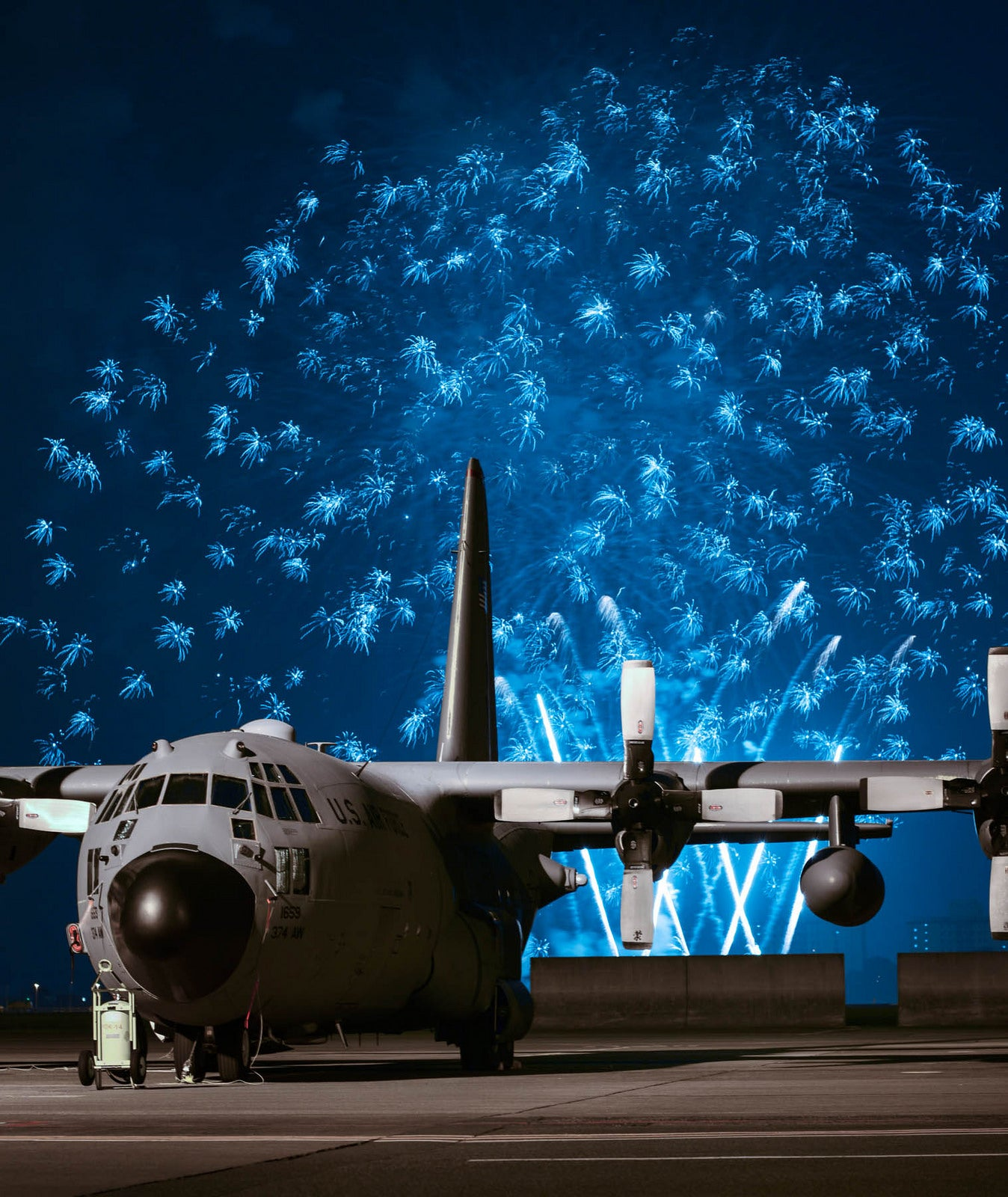 Electric blue fireworks light up the sky behind a C-130 Hercules plane