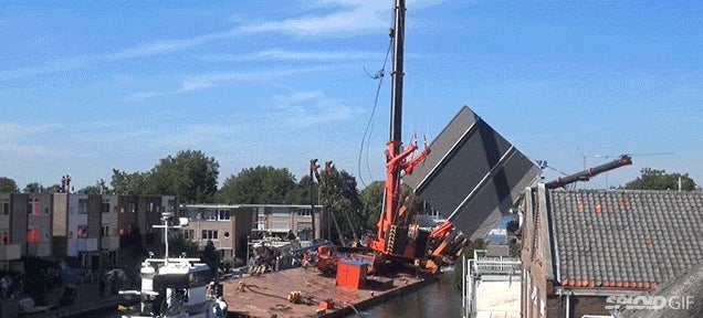 Two giant cranes holding a bridge collapse into nearby homes